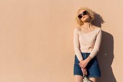 Den härliga unga flickan med krullning i solglasögon står nära väggen i solljus på solnedgången Royaltyfria Bilder