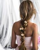Den härliga unga flickan med långt hår blommar mjukheten av gåtan i en flätad trådspringarebaksida Arkivbild