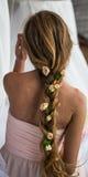 Den härliga unga flickan med långt hår blommar mjukheten av gåtan i en flätad trådspringarebaksida Royaltyfria Bilder