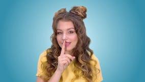 Den härliga unga flickan med långt hår sätter ett finger till hans kanter och visar en gest av tystnad stock video