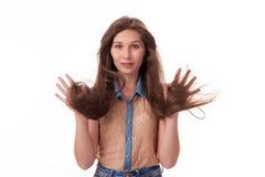 Den härliga unga flickan med långt hår visar likgiltiga sinnesrörelser - vakenhet Fotografera på en vit bakgrund arkivbild