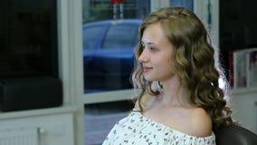 Den härliga unga flickan med långt lockigt blont hår och blåa ögon ser sig för makeup arkivfilmer