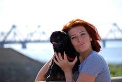 Den härliga unga flickan med röda håromfamningar på gatan av husdjuret en svart hund av aveln en mops Arkivfoto