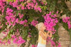 Den härliga unga flickan nära blommar Arkivfoto