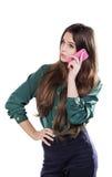 Den härliga unga flickan på en vit bakgrund är en rosa mobiltelefontelefonom Govorit leenden förvånadt Arkivbild