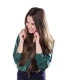Den härliga unga flickan på en vit bakgrund är en rosa mobiltelefontelefonom Govorit leenden förvånadt Fotografering för Bildbyråer