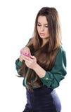Den härliga unga flickan på en vit bakgrund är en rosa mobiltelefontelefonom Govorit leenden förvånadt Royaltyfri Fotografi
