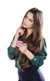Den härliga unga flickan på en vit bakgrund är en rosa mobiltelefontelefonom Govorit leenden förvånadt Arkivfoton