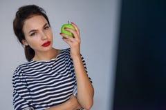 Den härliga unga flickan rymmer äpplet Arkivbilder