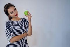 Den härliga unga flickan rymmer äpplet Royaltyfri Bild