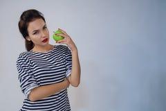 Den härliga unga flickan rymmer äpplet Arkivbild