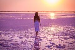 Den härliga unga flickan som går på, saltar sjön på solnedgången royaltyfria foton