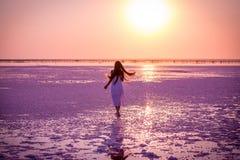 Den härliga unga flickan som går på, saltar sjön på solnedgången arkivfoto