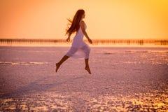Den härliga unga flickan som hoppar på, saltar sjön på solnedgången arkivfoto