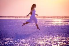 Den härliga unga flickan som hoppar på, saltar sjön på solnedgången royaltyfria foton