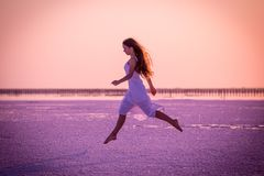 Den härliga unga flickan som hoppar på, saltar sjön på solnedgången royaltyfri fotografi