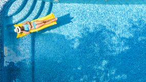 Den härliga unga flickan som kopplar av i simbassängen, bad på den uppblåsbara madrassen och, har gyckel i vatten på familjsemest arkivfoton