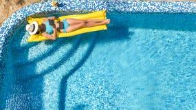 Den härliga unga flickan som kopplar av i simbassängen, bad på den uppblåsbara madrassen och, har gyckel i vatten på familjsemest royaltyfri bild