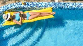 Den härliga unga flickan som kopplar av i simbassängen, bad på den uppblåsbara madrassen och, har gyckel i vatten på familjsemest royaltyfria bilder