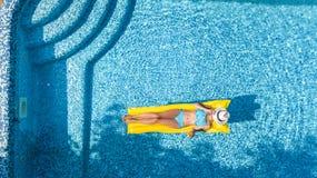 Den härliga unga flickan som kopplar av i simbassängen, bad på den uppblåsbara madrassen och, har gyckel i vatten på familjsemest arkivfoto