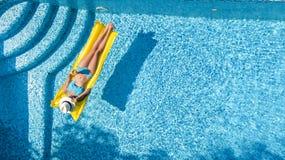 Den härliga unga flickan som kopplar av i simbassängen, bad på den uppblåsbara madrassen och, har gyckel i vatten på familjsemest royaltyfria foton