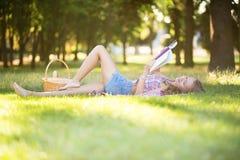 Den härliga unga flickan som läser en bok parkerar in Royaltyfria Bilder