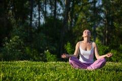 Den härliga unga flickan som in mediterar, parkerar Royaltyfri Foto