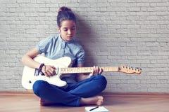 Den härliga unga flickan spelar gitarren Royaltyfria Bilder