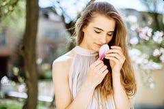 Den härliga unga flickan står bland blomningträden blommar white Vårflicka med hennes hår i en beige klänning arkivfoton