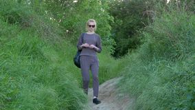 Den härliga unga flickan stiger ned en bana på en kulle mycket av grönt gräs stock video