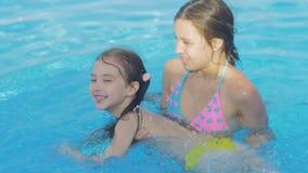 Den härliga unga flickan undervisar hennes lilla syster att simma i pölen arkivfilmer