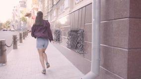 Den härliga unga gladlynta flickan går i staden Körningar som svänger hans händer arkivfilmer