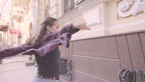 Den härliga unga gladlynta flickan går i staden Körningar som svänger hans händer stock video