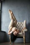 Den härliga unga gymnasten på en stol tog ett ovanligt mode poserar Arkivfoton