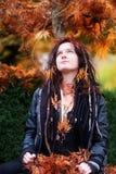 Den härliga unga individen, den excentriska kvinnan, med dreadlocks, piercingen och tatueringen som bär ett svartläderomslag, sit fotografering för bildbyråer