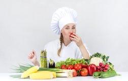 Den härliga unga kockkvinnan förbereder sig och dekorera smaklig mat in Royaltyfri Bild