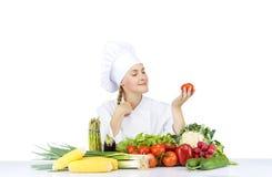 Den härliga unga kockkvinnan förbereder sig och dekorera smaklig mat in Arkivfoton