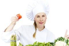 Den härliga unga kockkvinnan förbereder sig och dekorera smaklig mat in Royaltyfri Foto
