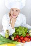 Den härliga unga kockkvinnan förbereder sig och dekorera smaklig mat in Arkivfoto