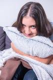 Den härliga unga kvinnan är den avslappnande krökningen över hennes kudde royaltyfri fotografi