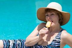 Den härliga unga kvinnan äter glass royaltyfri foto