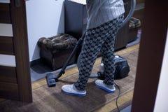 Den härliga unga kvinnan använder en dammsugare, medan göra ren golvet hemma royaltyfri foto
