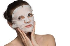 Den härliga unga kvinnan applicerar en kosmetisk maskering på en framsida på a arkivfoto