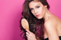 Kvinnan borstar hår Arkivfoto