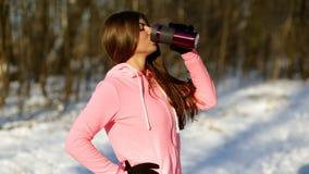 Den härliga unga kvinnan dricker te, når han har joggat i vinterskogen arkivfilmer