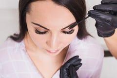 Den härliga unga kvinnan får ögonbrynkorrigeringstillvägagångssätt arkivbilder