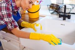 Den härliga unga kvinnan gör att göra ren huset Flickalokalvårdki Royaltyfri Fotografi