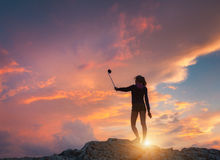 Den härliga unga kvinnan gör selfie för Instagram på solnedgången arkivbilder