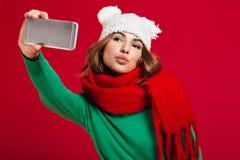Den härliga unga kvinnan gör selfie vid telefonen som blåser kyssar Arkivfoton