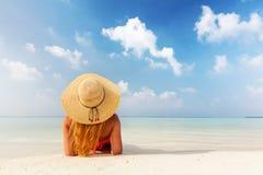 Den härliga unga kvinnan, i att ligga för sunhat, kopplade av på den tropiska stranden i Maldiverna Arkivbild